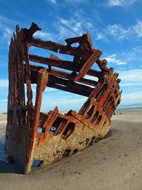 Rusty Wreckage Of A Ship On A Beach On The Oregon Coast Usa