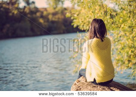 Woman Sitting Next To A River