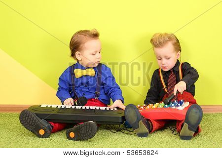 Two mods boy in bright clothes with a toy piano and metallophone