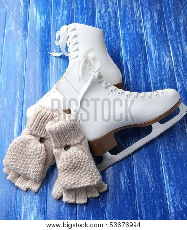 Wool fingerless gloves and skates for figure skating, on wooden background