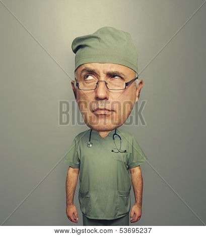 pensive doctor with bighead over grey background