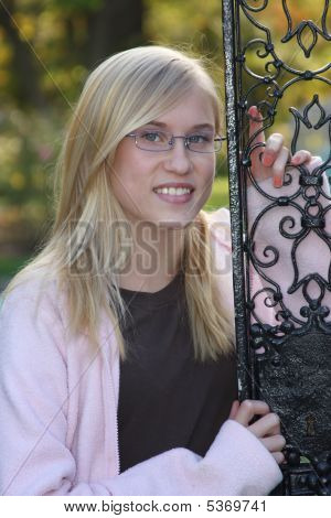 Young Blonde Teen Posing By A Gate