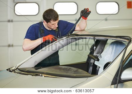 Automobile glazier worker disassembling windscreen or windshield of a car in auto service station garage before installation poster