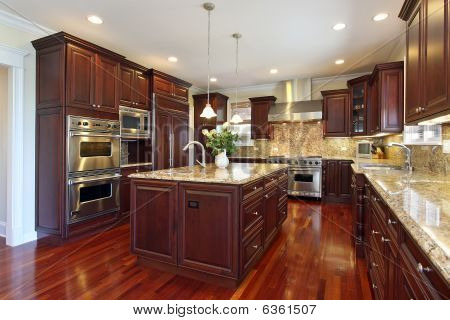 Kitchen in luxury home with cherry wood cabinetry poster