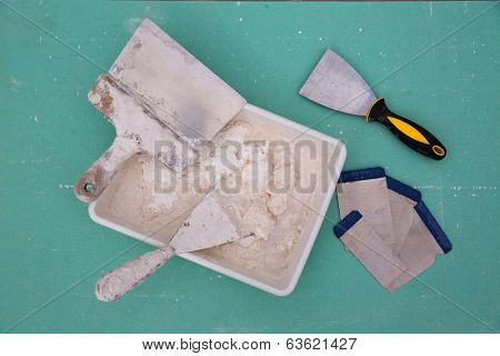 Platering tools for plaster like plaste trowel spatula on green drywall plasterboard