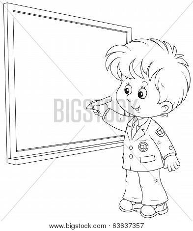 Schoolboy writes on the blackboard
