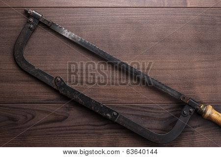 old hacksaw rusty on wooden background