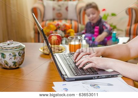 Woman hands writing in notebook and boy playing