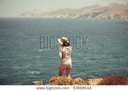 Female Teenager With Straw Hat Standing On A Cliff