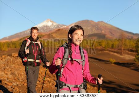 People hiking - healthy active lifestyle couple. Hikers walking in beautiful mountain nature landscape. Woman and man hikers walking during hike on volcano Teide, Tenerife, Canary Islands, Spain.