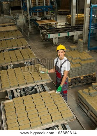 Young worker near conveyor belt with paving stone  on a factory