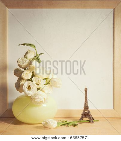 ikebana and vintage photo-frame on table