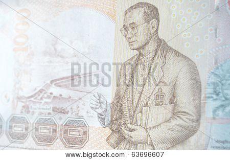 His Majesty King Bhumibol Adulyadej (Rama IX) of Thailand holding a SLR camera with the Pa Sak Jolasid Dam.  1000 Thai Baht banknote.  Used banknote, photographed at an angle. poster