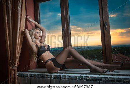 Attractive sexy blonde in black lingerie posing provocatively in window frame. Sensual woman