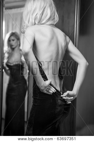 Young beautiful luxurious woman zipping up her long elegant black dress looking in a large mirror