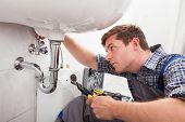 Portrait of male plumber fixing a sink in bathroom poster