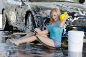 A blonde model washes her car at a local car wash poster