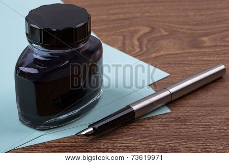Inkwell and fountain pen on wooden texture.