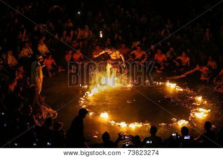 BALI, INDONESIA - SEPTEMBER 19, 2014: Hanuman puts out the fire during a performance of the traditional Balinese Kecak Fire Dance at the Uluwatu Temple in Bali.