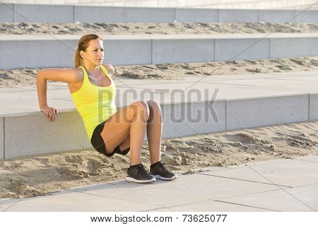 Young, athletic woman excercising her upper body during a bootcamp training session on a beach boulevard
