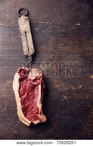 Raw Fresh Meat Ribeye Steak And Vintage Steelyard On Dark Background
