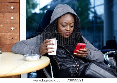 Black Woman At Cafe Having Coffee While Texting