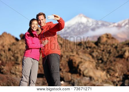 Couple taking selfie hiking in beautiful nature with smart phone. Happy couple walking enjoying view and taking pictures with smartphone. Man and woman by Volcano Teide on Tenerife, Canary Islands.