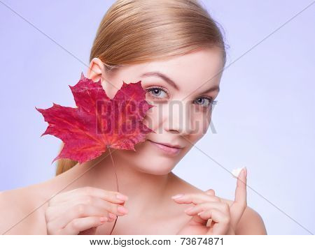 Skincare habits. Face of young woman with leaf as symbol of red capillary skin on violet. Girl taking care of her dry complexion applying moisturizing cream. Beauty treatment. poster