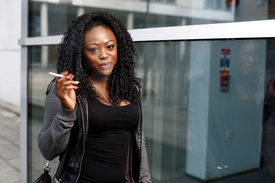 Smiling African Woman Smoking A Cigarette