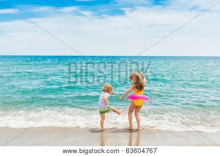 Two kids having fun on summer vacation, playing in the sea poster