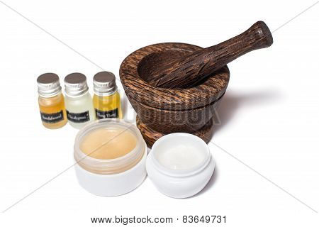 Wooden pounder with bottles of organic oils and cream isolated