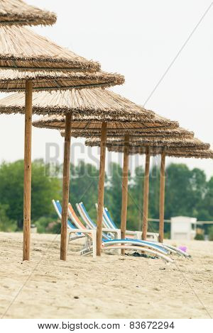 Row Of Straw Umbrellas And Suneds At A Beach. Photo With Untraditional Color Rendering For Artisctic