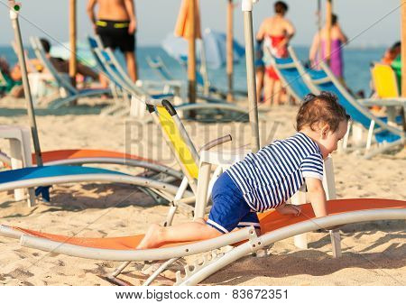 Sweet Toddler Dressed As A Sailor Crawling On A Sunbed On A Beach With Other People In Defocussed Ba