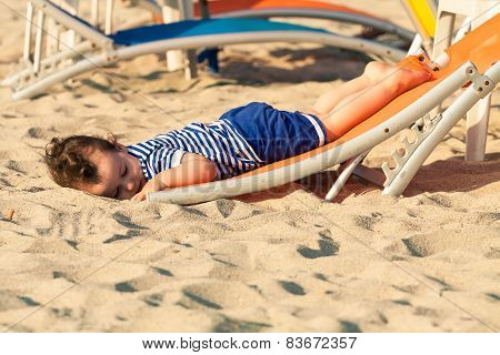 Sweet Toddler Dressed As A Sailor Lying From A Top Of A Sunbed On A Beach And Looking As He Is Drunk
