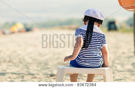 Sweet Toddler Dressed As A Sailor Sitting On A Plastic Table On A Beach With View From His Back. Pho
