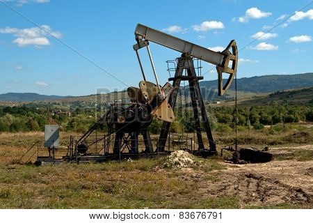 an oil pump is on a background mountains poster