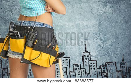 Woman in tool belt against stone wall with sketch of city on it