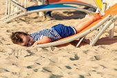 Sweet toddler dressed as a sailor lying from a top of a sunbed on a beach and looking as he is drunk. Photo with untraditional color rendering for artistic look poster
