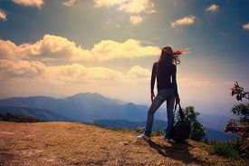 Woman Traveler With Backpack Looking At Mountain Landscape And Sky In Evening Time