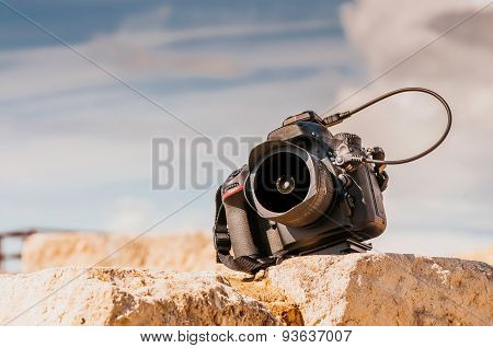 Professional digital camera on top of the stone block. Close up photo.