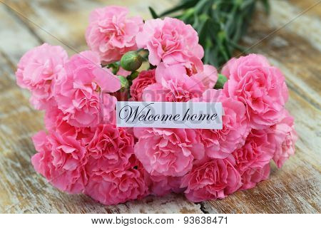 Welcome home card with pink carnations on rustic wooden surface poster