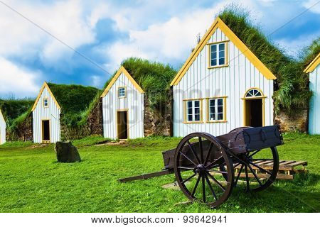 The village first settlers in Iceland. The reconstituted village - Pioneer Museum - Viking. Old wooden two-wheeled carriage on front lawn of the house