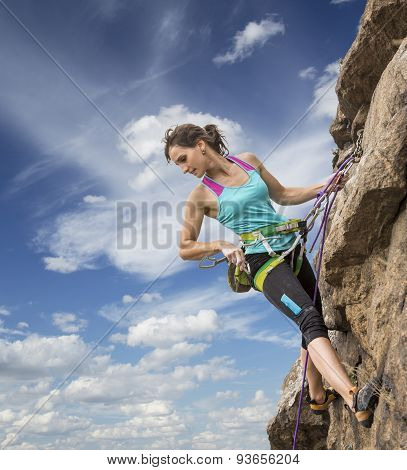 Female rock climber hanging over the abyss Brave and confident female rock climber enjoys hanging on her hand over the deep abyss poster