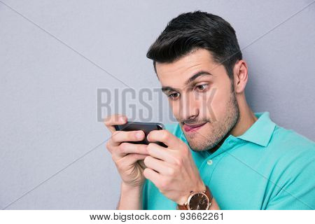 Funny young man using smartphone over gray backgrpound