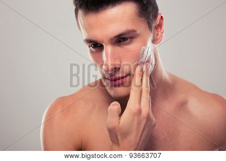 Handsome man applying facial cream over gray background
