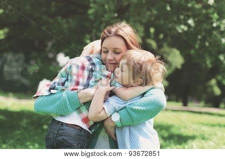 Family happiness! Happy mother tenderly embracing his two sons in spring day warm feelings of the mother moment of life happy family on nature poster