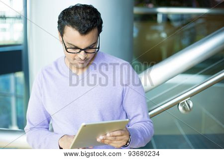 Serious Man Looking At Tablet