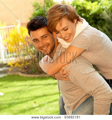 Young couple having fun outdoors. Man carrying girlfriend on his back, both smiling.