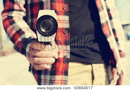 closeup of a young man pointing a Super 8 camera at the observer like it was a gun