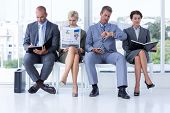 Business people waiting to be called into interview at the office poster